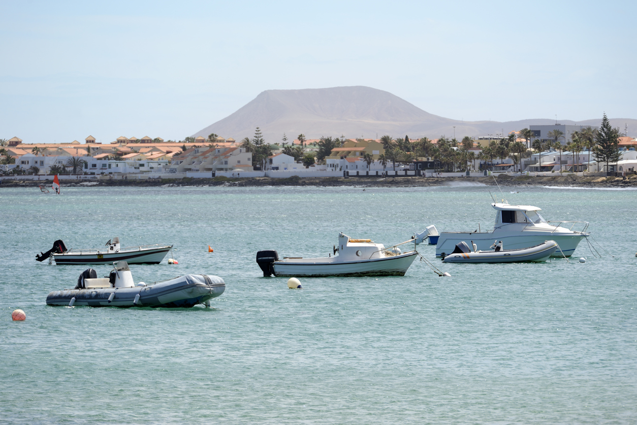 Coastline of Corralejo with boats and volcanic crater, Fuerteventura, Canary Islands, Spain.