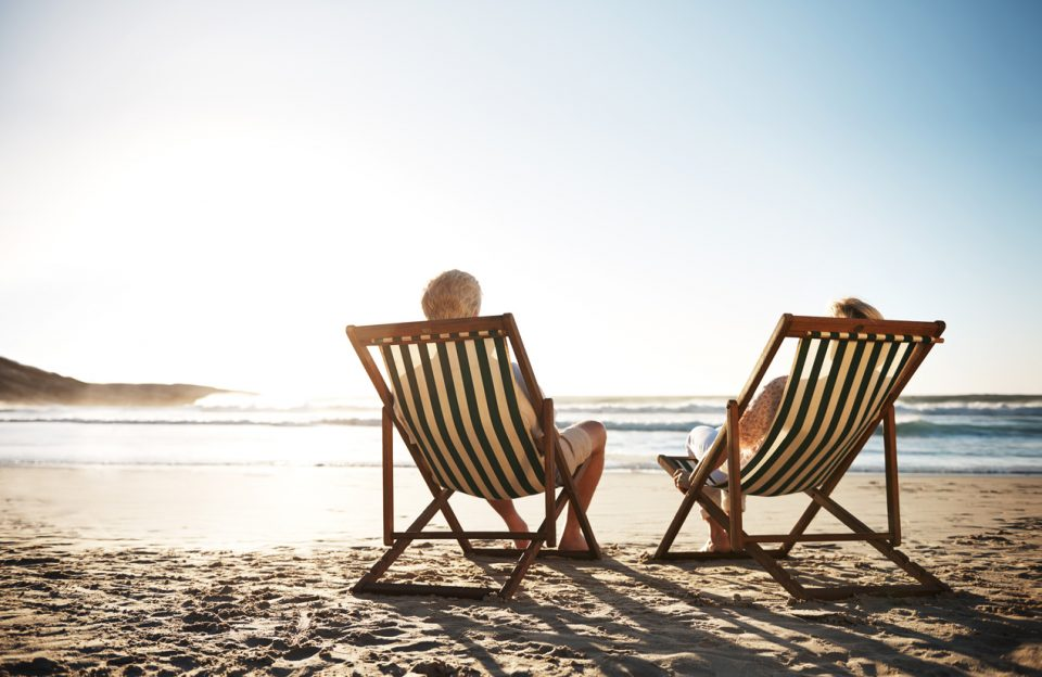 Rearview shot of a senior couple relaxing in beach chairs while looking at the view over the water