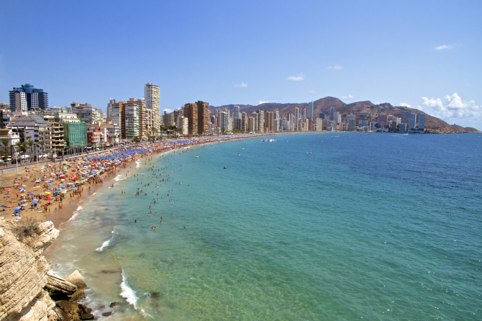 Wide angle of the Iconic hotel skyscraper skyline of Benidorm and Levante Beach, with unrecognisable people enjoying the sunshine and the Mediterranean Sea in Benidorm on the Costa Blanca, province of Alicante in Spain.