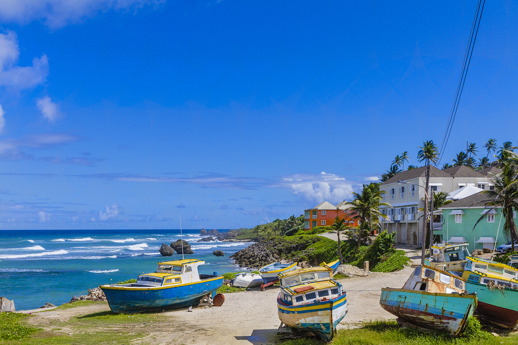 Colorful boats under repair at Tent Bay, a picturesque bay on the east coast of Barbados, facing the Atlantic Ocean.