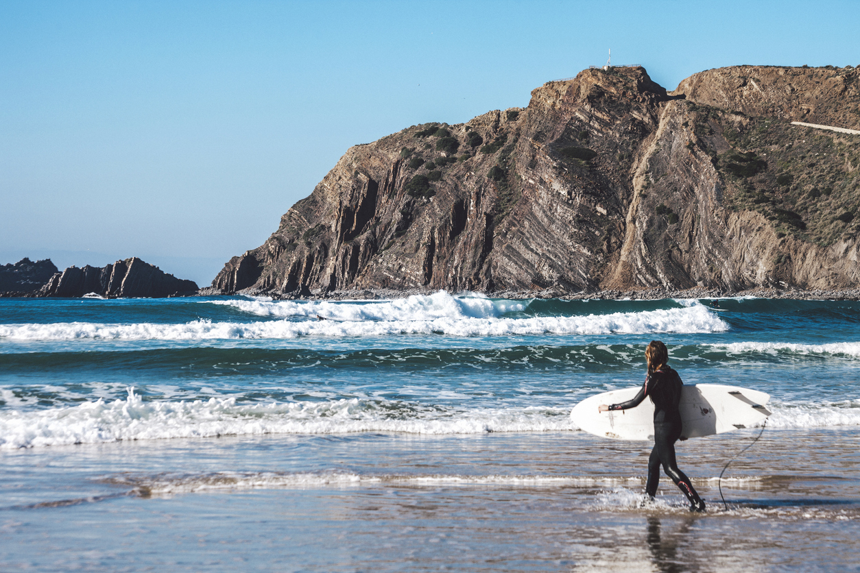 Arrifana, Portugal - December 25, 2014: Arrifana beach is popular destination even in winter time. Surfers enjoying big waves on a sunny day.
