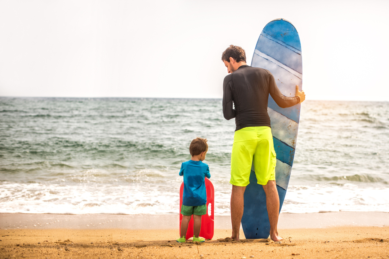 Surfer dad, and his two year old son holding their surfboards while standing on the beach by the sea