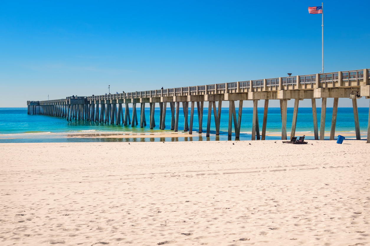 Photo of the City Pier and white sand beach at Panama City Beach, Florida, USA on a clear blue sky day.