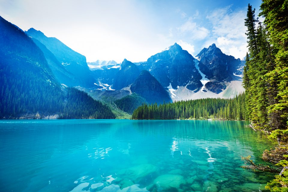 Lake Moraine in the Banff National Park, Alberta, Canada, features clear emerald water and snow-capped peaks of the Canadian Rockies mountain range. The scenic landscape is a famous place and a favorite tourist travel destination for North American great outdoors nature vacations. horizontal format with copy space and no people.