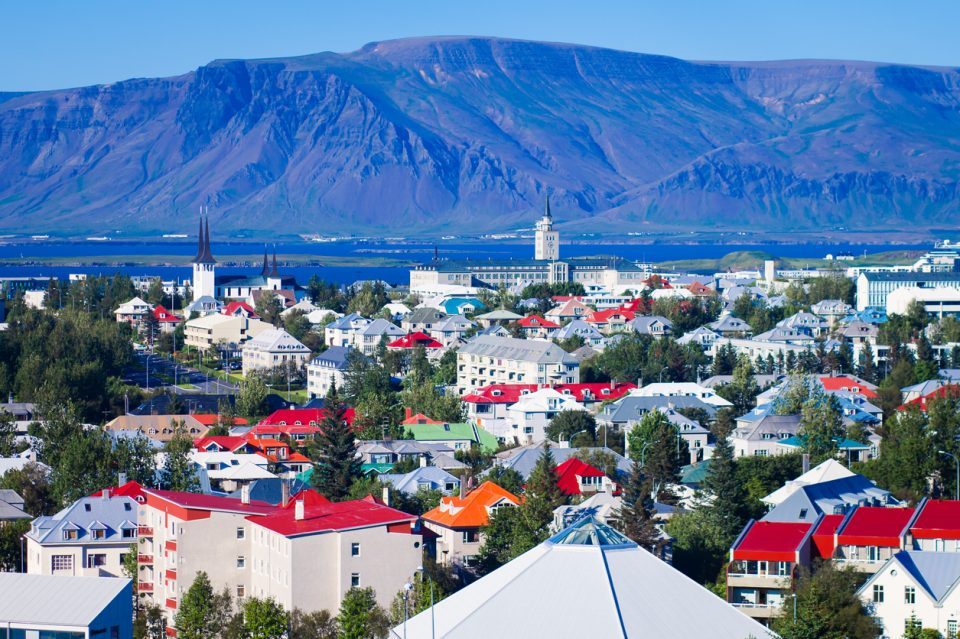 Beautiful summer super wide-angle aerial view of Reykjavik, Iceland with harbor and skyline mountains and scenery beyond the city, seen from the observation tower of hallgrimskirkja church with blue sky in sunny day.