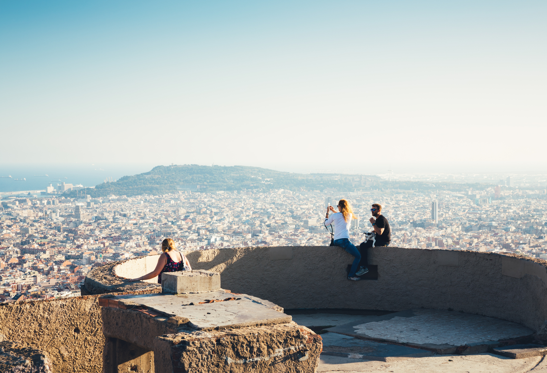 Barcelona, Spain - September 28, 2016: Tourists on Bunkers del Carmel (Búnquers del Carmel) enjoying the viewpoint in Barcelona. Young couple is sitting on the wall. Woman photographing the Barcelona cityscape with Montjoic hill and sea in the distance.