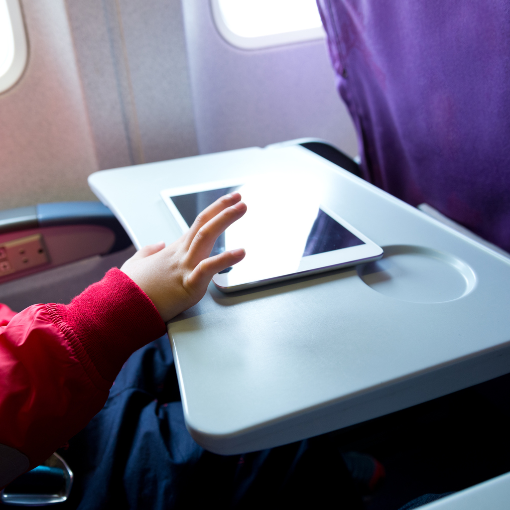 Little boy playing with a tablet computer in plane