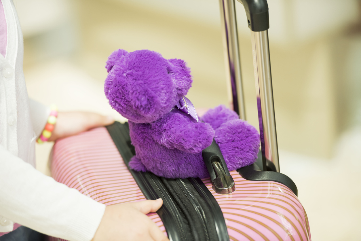 Unrecognizable child with suitcase and a toy, selective focus