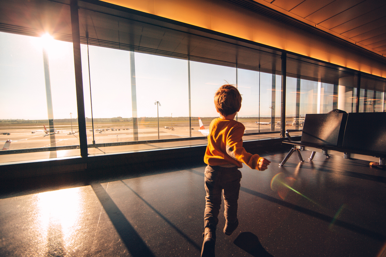 Young boy is having fun in an airport lounge while waiting for a flight