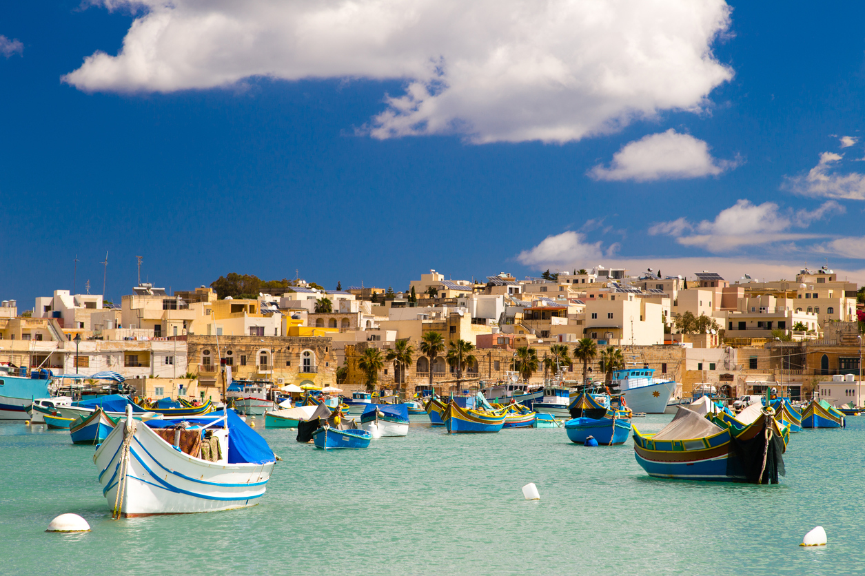 Colorful, traditional fishing boats against the backdrop of Marsaxlokk village in the mediterranean island of Malta. See portfolio for more.