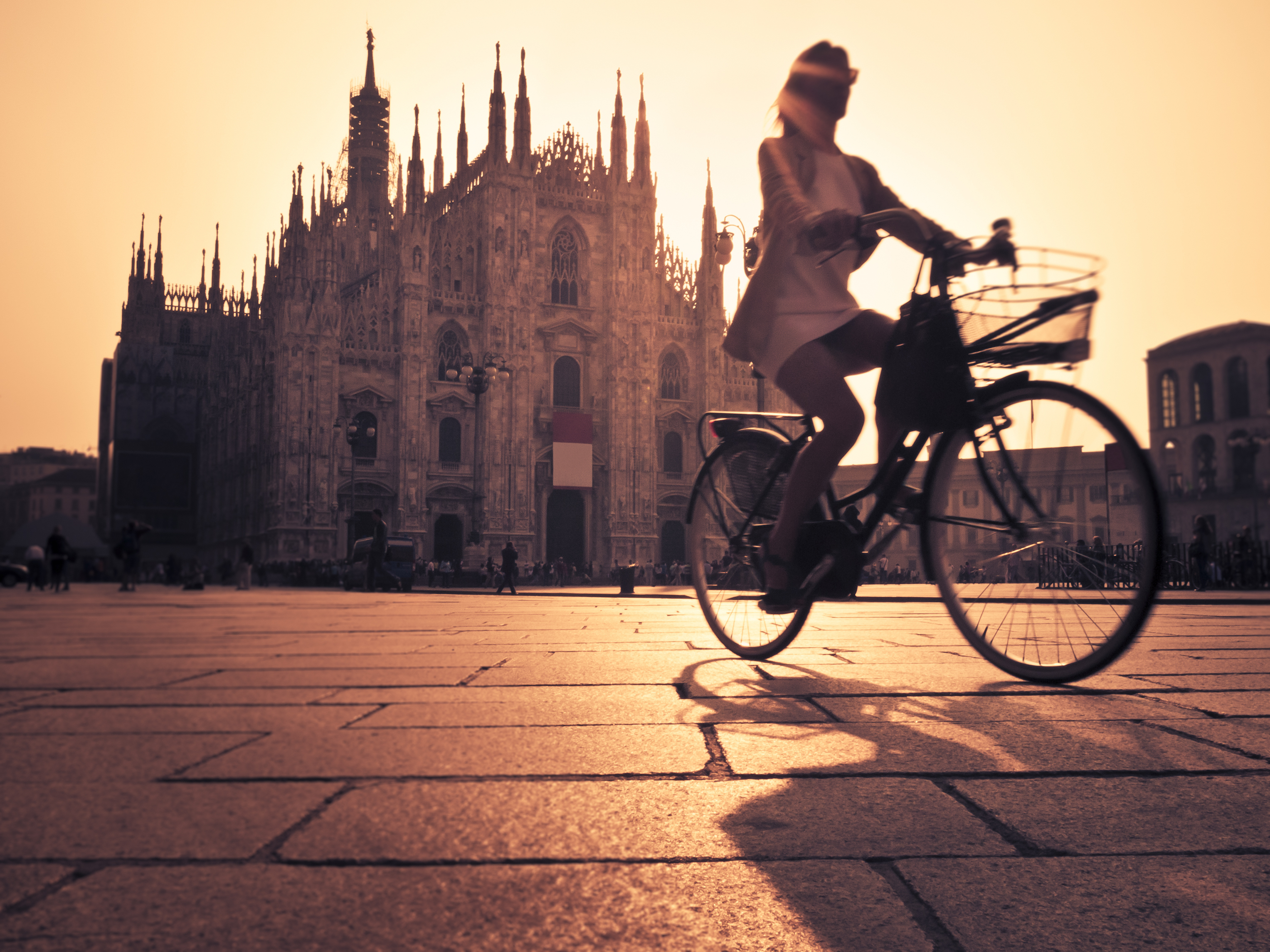 Riding A Bicycle In Milan City At Sunset