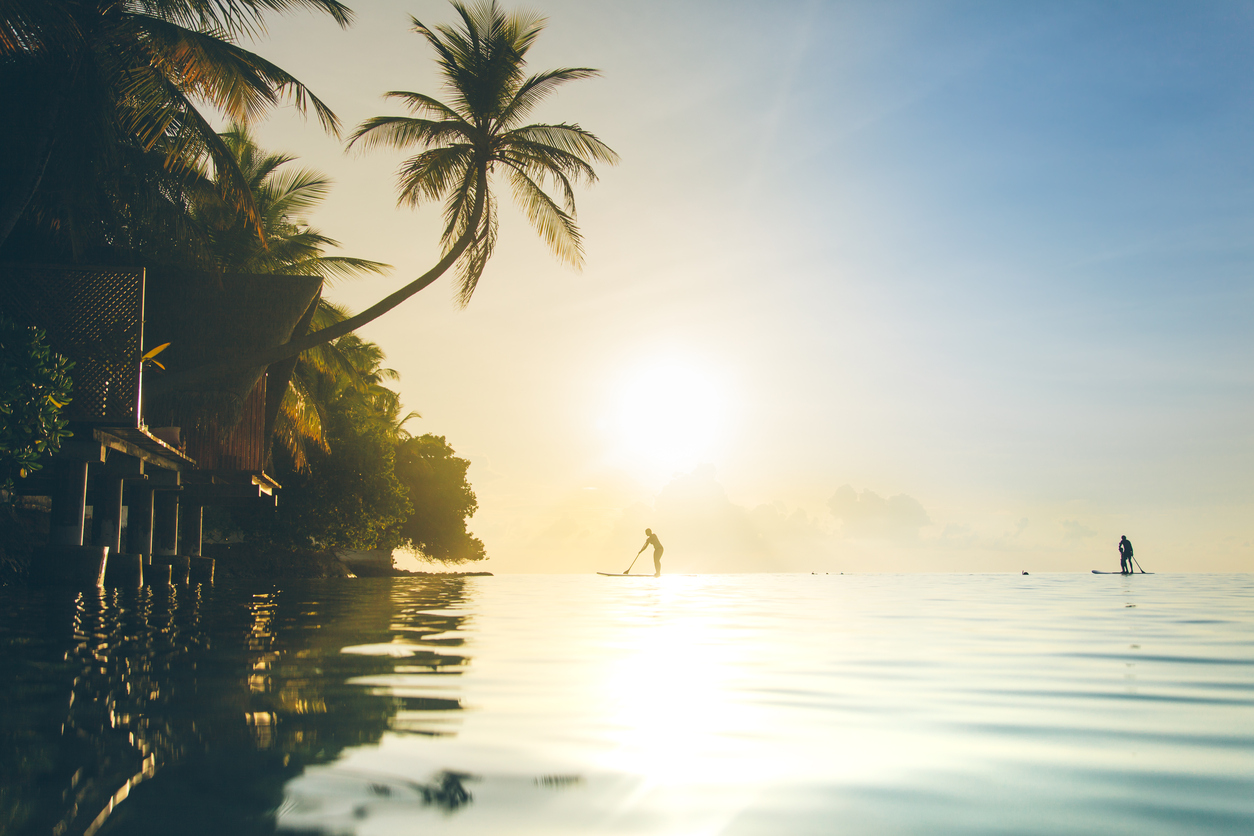 People (silhouettes), paddling towards a beautiful sunset at the tranquil Maldives sea, with calm water and palms.