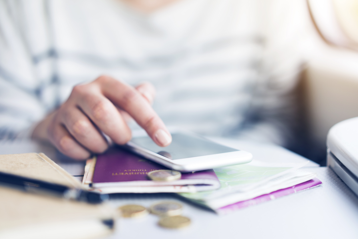 Woman hand using smart phone, touching on the screen with her finger. Passport, smartphone, money, and a map on the desk out of focus. Focus on finger.