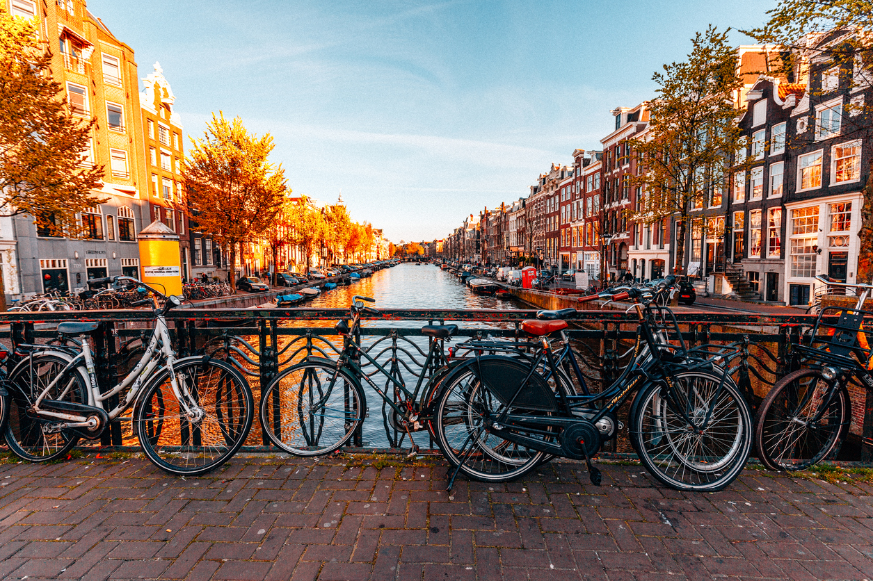 Amsterdam city scene with many bike parkes on typical water canal and bridge in sunny day