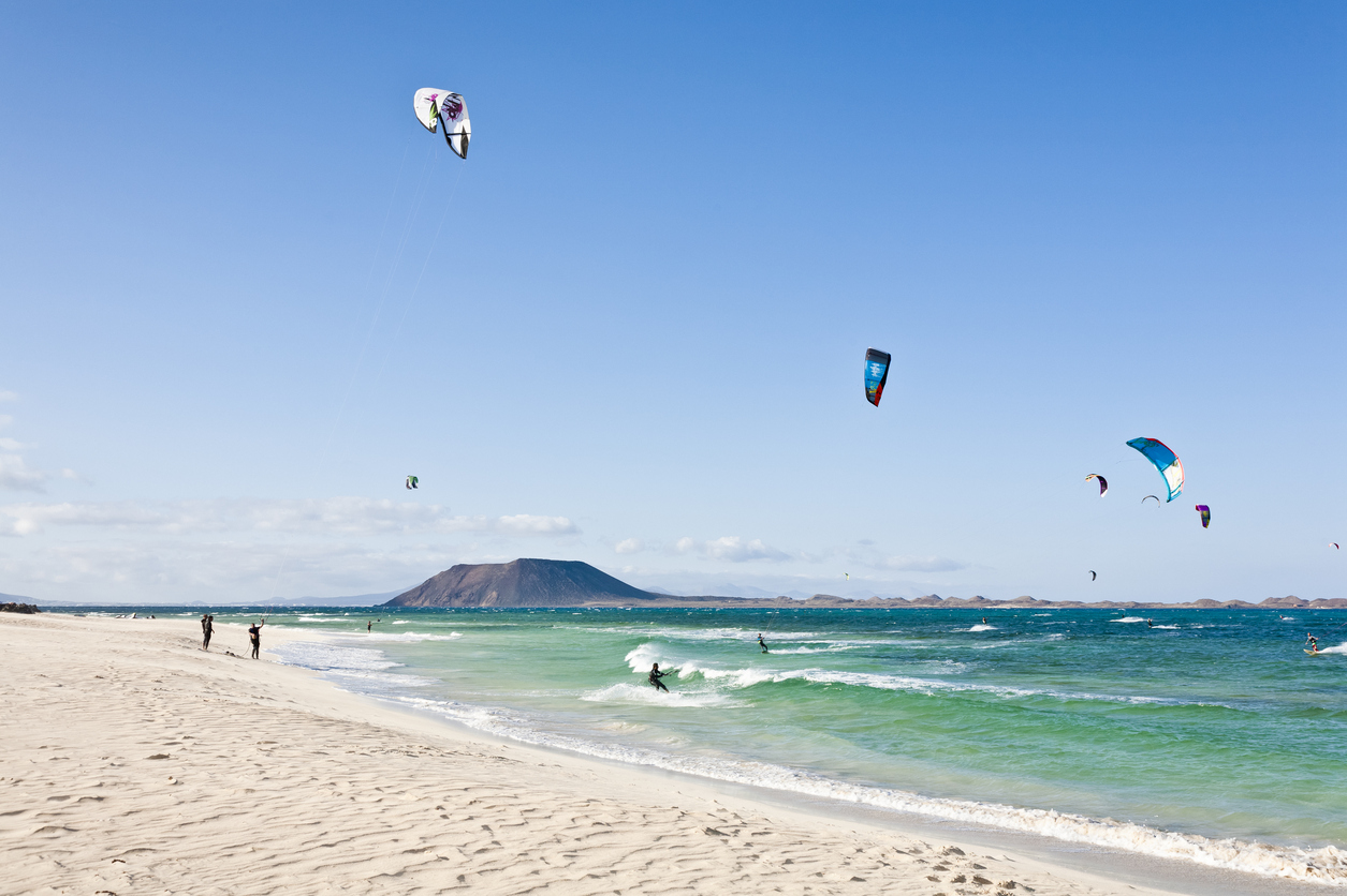 """Corralejo, Fuerteventura - May 29, 2012: Kite surfing in Fuerteventura. The image was taking on Corralejo beach, a perfect place for surfers. Everyday this part of the island is covered by strong wind."""