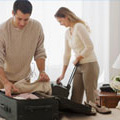 A couple packing clothes into a suitcase for their holiday